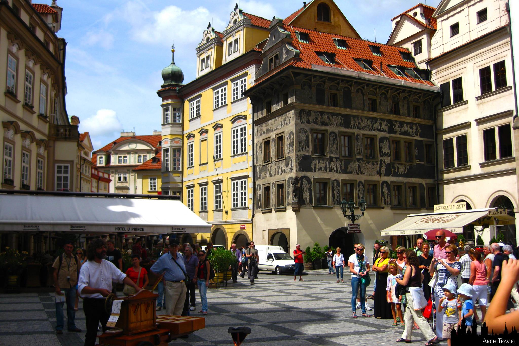 słoneczny dzień na Placu Staromiejskim w Pradze, po lewej grajek, po prawej wielu gapiów