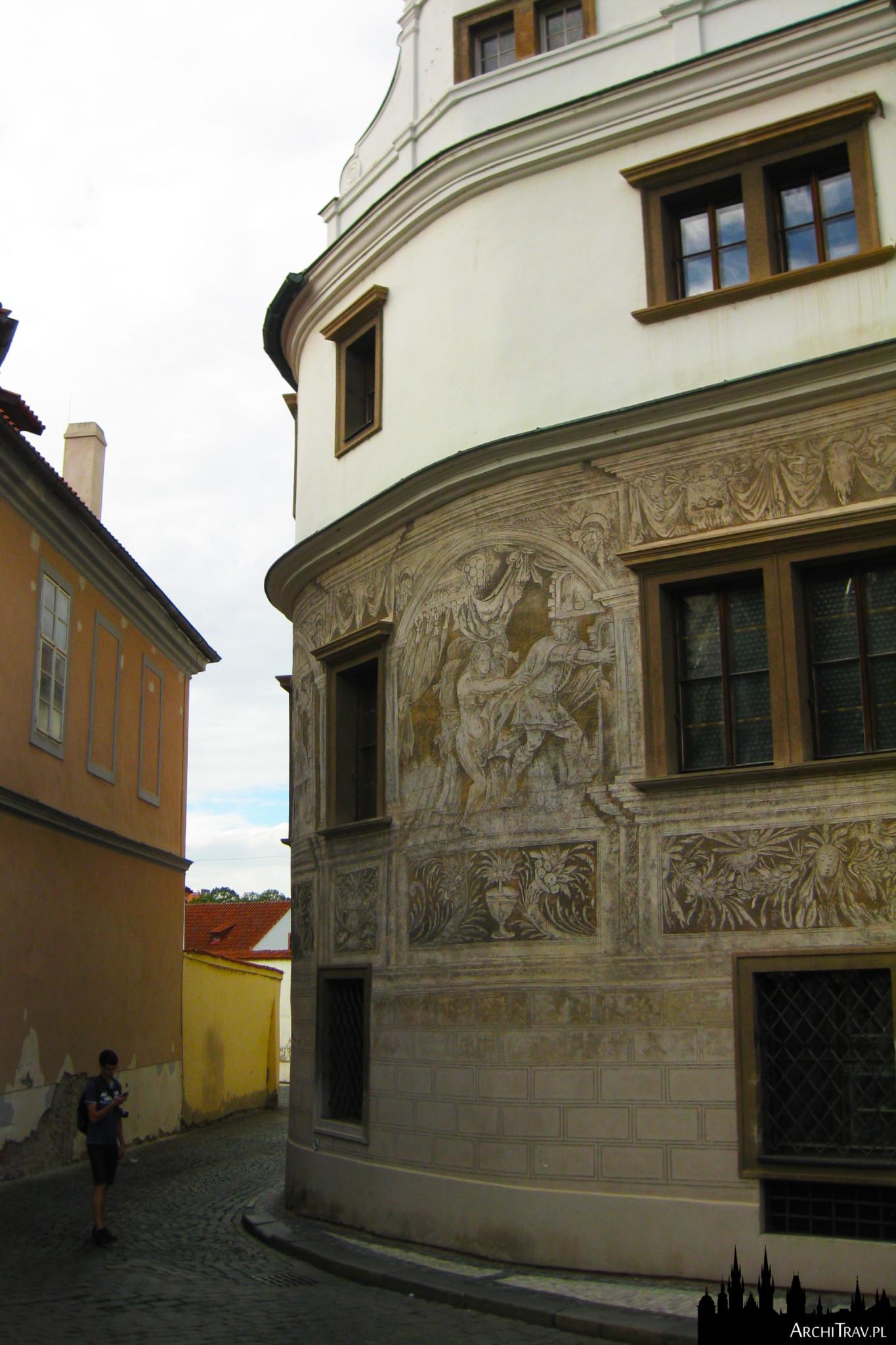 uliczka w Pradze, na pierwszym planie zaokrąglony budynek, a na nim freski