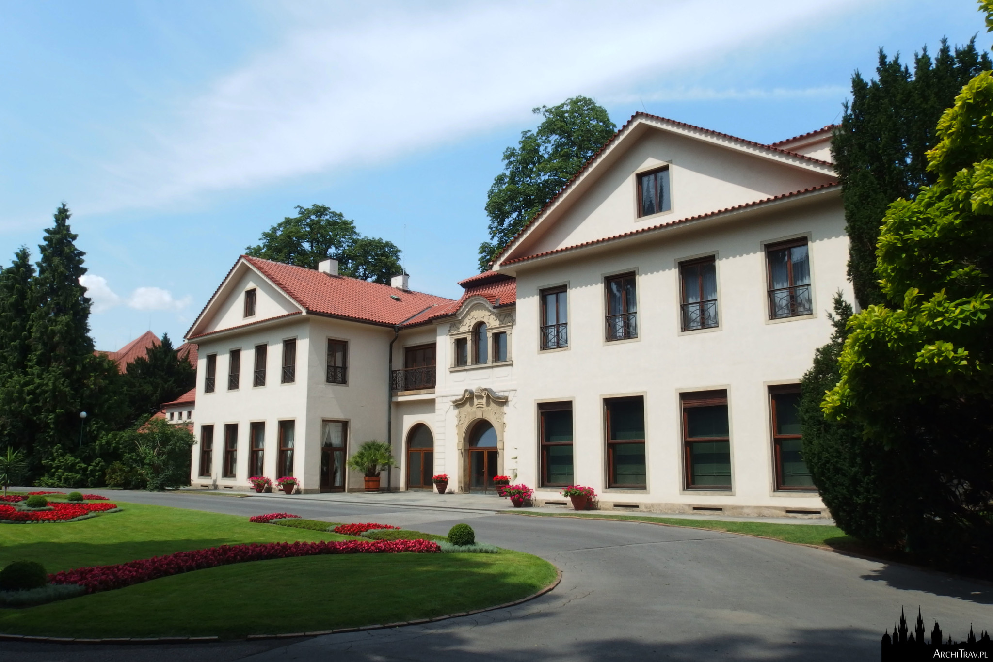Domek Prezydencki w Pradze - 3-kondygnacyjny budynek o jasnej elewacji, na froncie przystrzyżony trawnik z czerwonymi rabatami