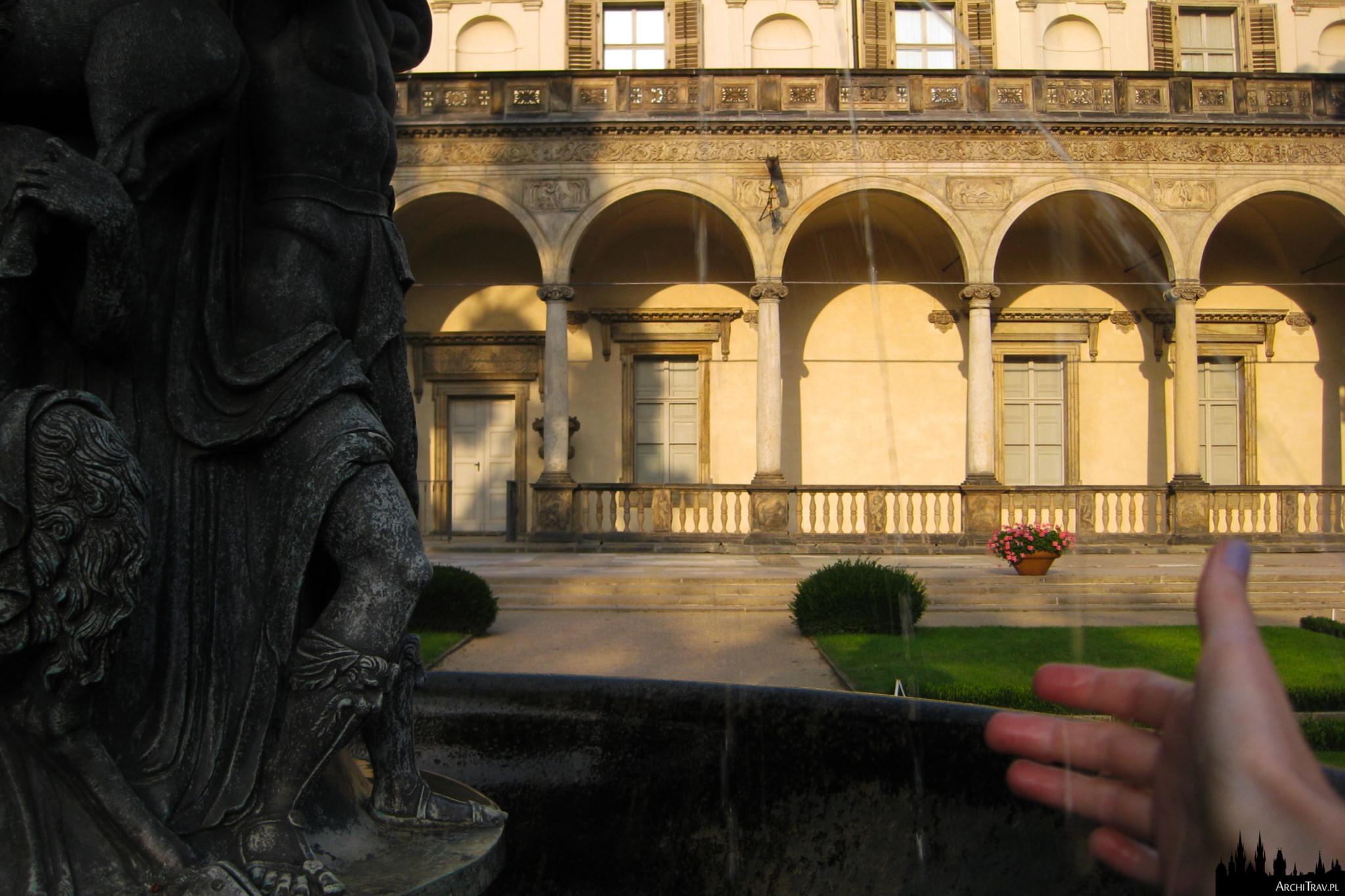 zbliżenie na detal fontanny, po prawej strumyki wody i wystawiona do nich ręka, perspektywę zamyka część budynku Belwederu