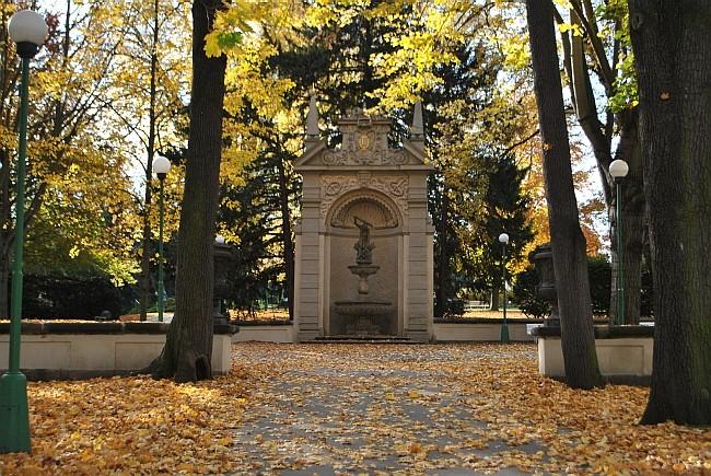 fontanna Herkules w Ogrodach Królewskich w Pradze - jesień, żółte liście, dużo już leży na ziemi, po środku barokowa nisza, a w niej ekspresyjna rzeźba Herkulesa