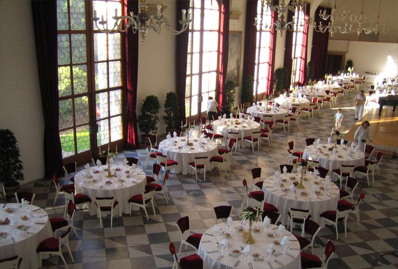 obszerna i wysoka sala z wysokimi oknami i ułożonymi okrągłymi stołami na uroczystość - dawna Sala do gry w piłkę w Ogrodach Królewskich w Pradze