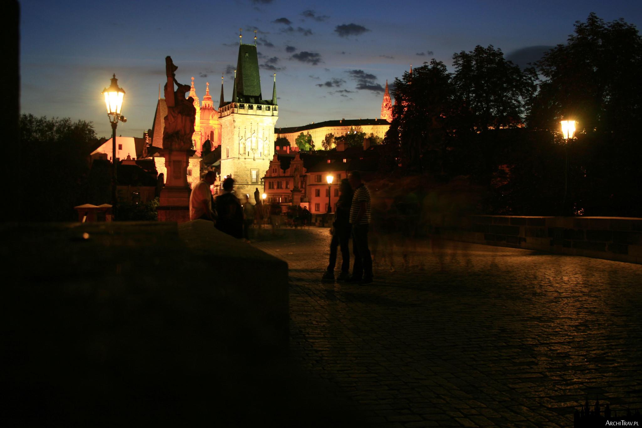 Most Karola w Pradze w nocy, mocno oświetlona Wieża Małostrańska