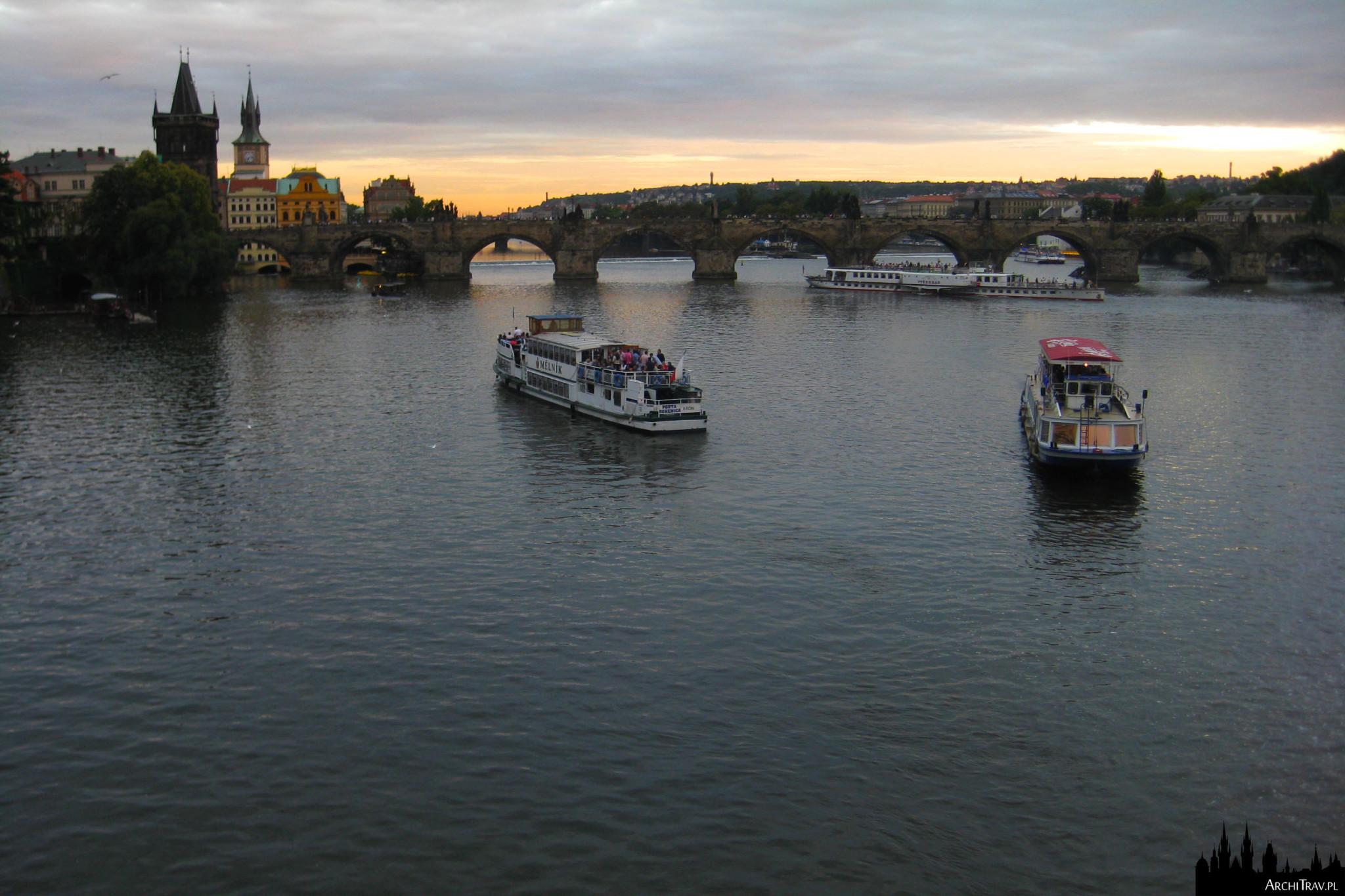 widok na Wełtawę, płynie kilka stateczków, w oddali Most Karola, zachód słońca