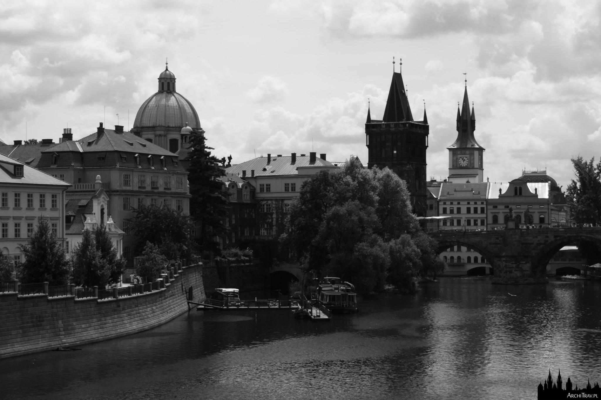 czarno białe zdjęcie prawego brzegu Wełtawy, widok na Wieżę Staromiejską i po prawej Most Karola