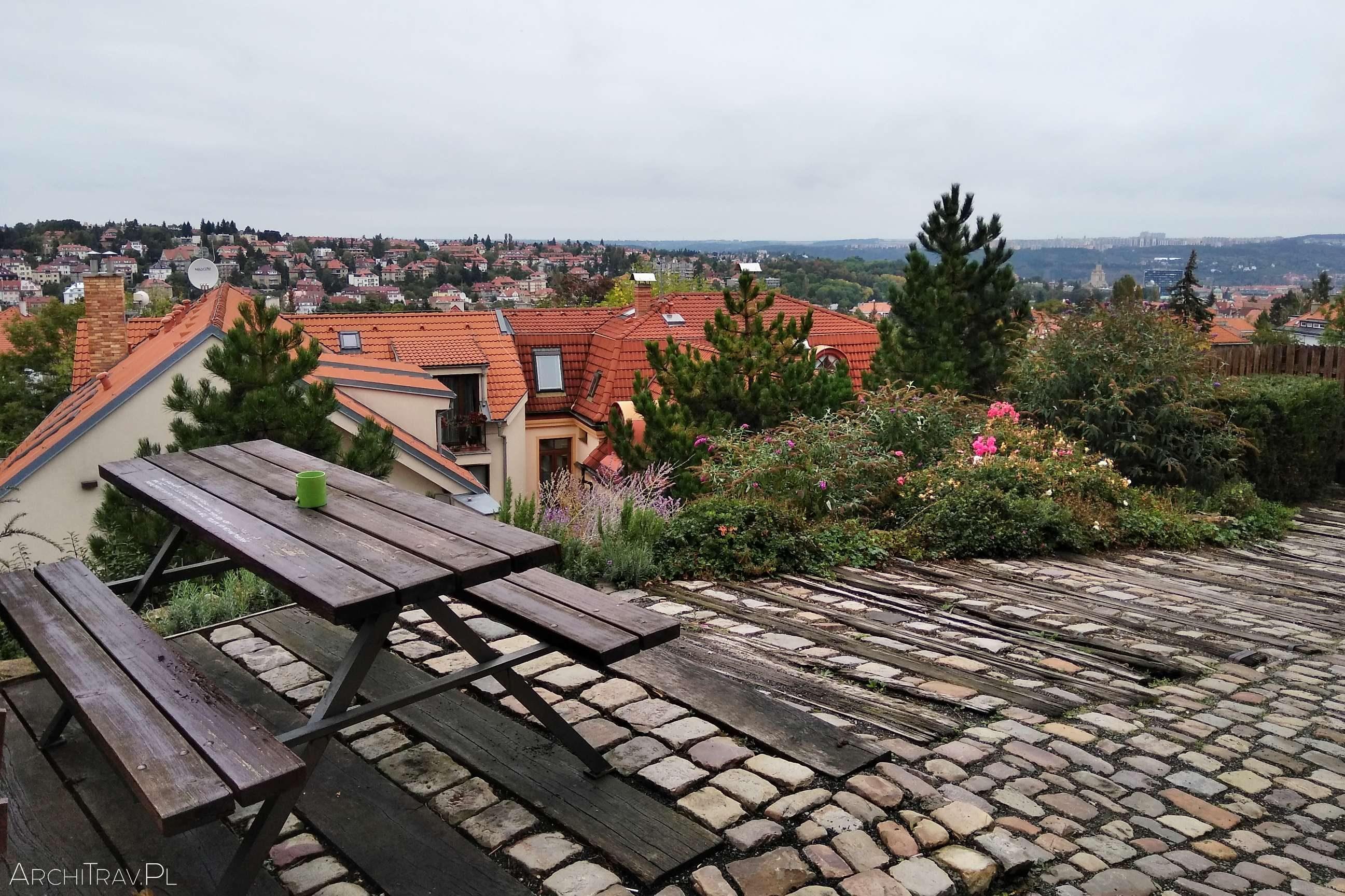 widok na Pragę z góry, na pierwszym planie ławeczki ze stołem